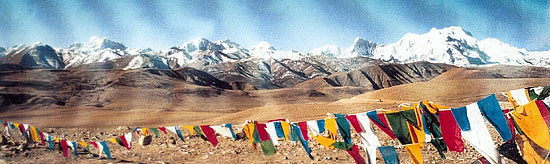 Tibetan prayer flags strung along the roadside in eastern Tibet with the snow-covered himalayan peaks in the background.  Mouseover to Tibetan Prayer flags and cairns of mani prayer stones left on a high  mountain pass.